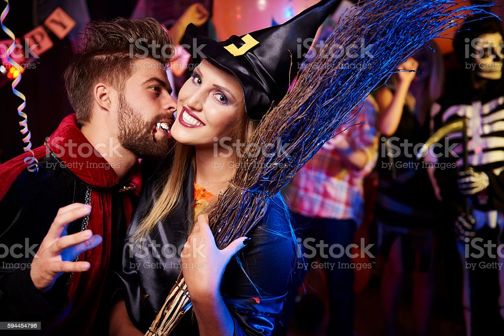 Vampire trying to bite his girlfriend stock photo