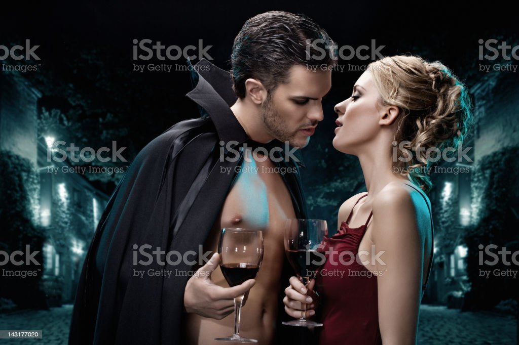 vampires couple holding glasses with blood stock photo