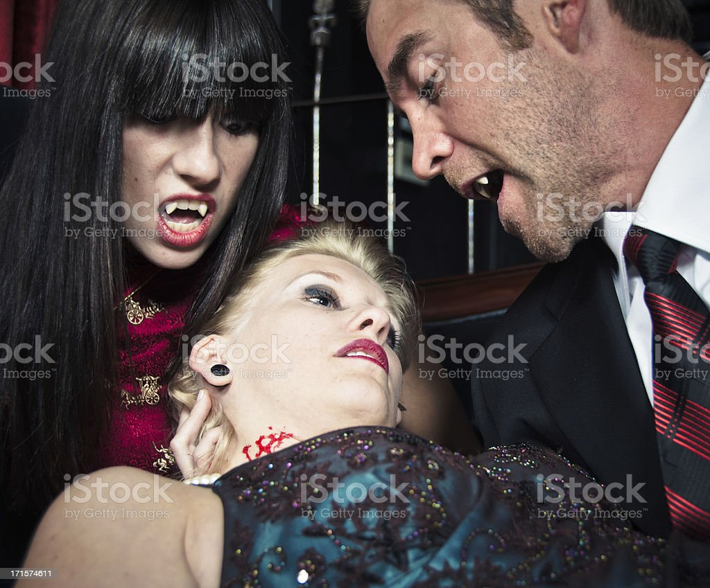 Vampires feeding on a young woman royalty-free stock photo