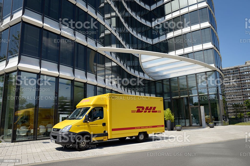 DHL van in front of a modern office building stock photo