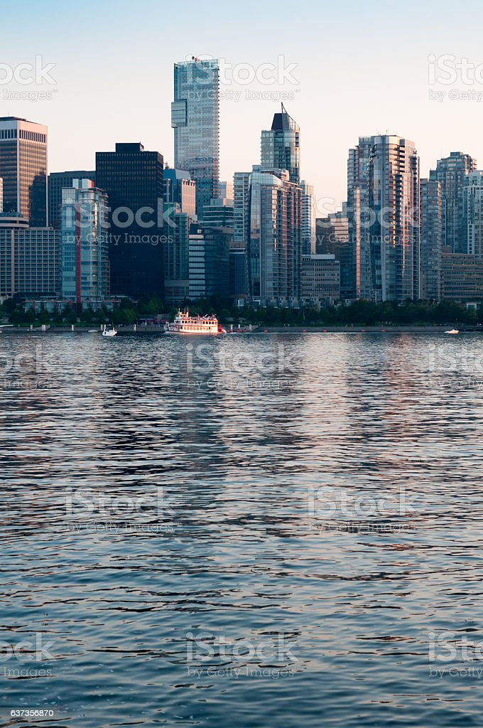 Vancouver harbour tour boat at dusk and urban skyline stock photo