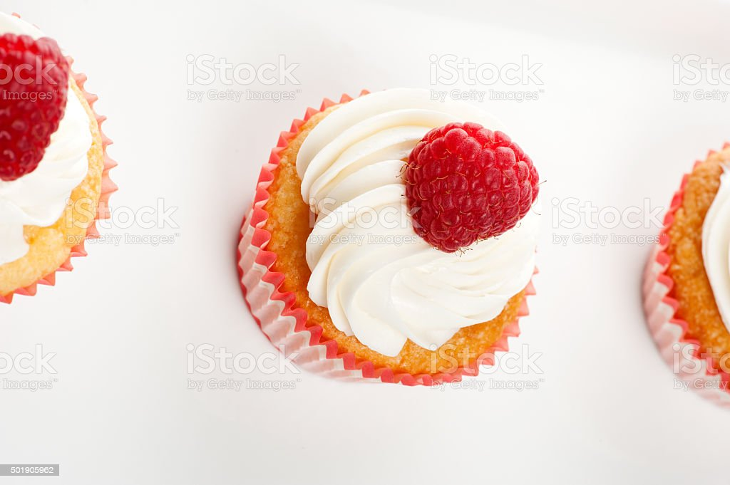 Vanilla Cupcakes with cream and a red berry on top stock photo