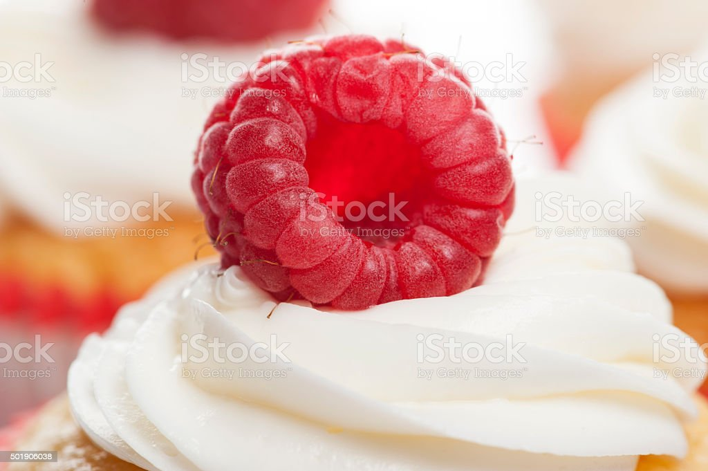 Vanilla Cupcakes with cream and a red cherry on top stock photo
