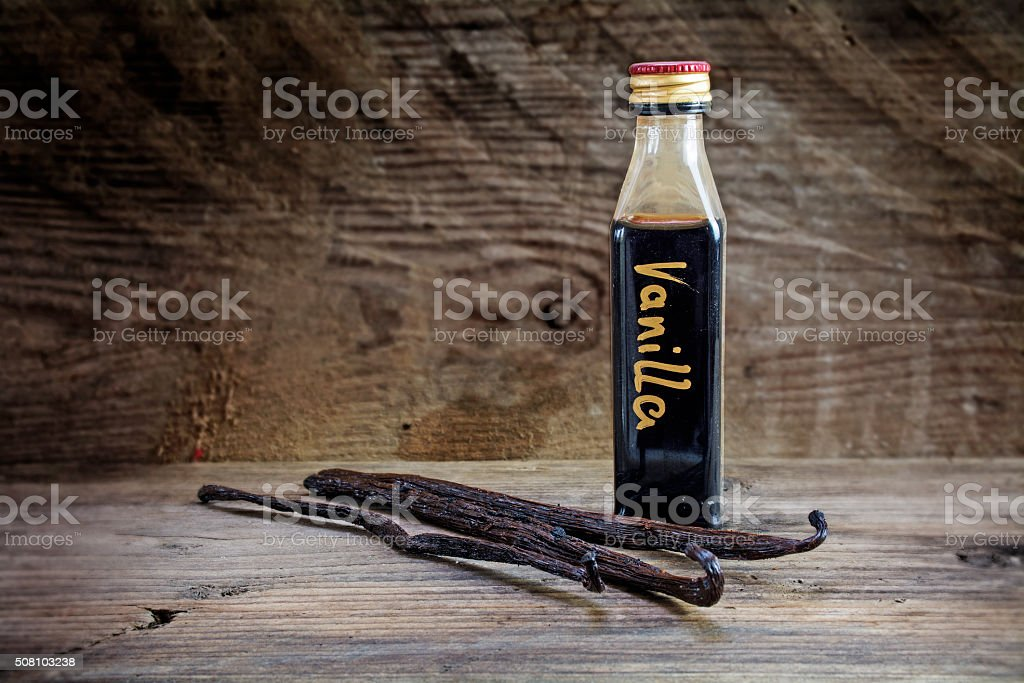 vanilla extract in a bottle and pods on rustic wood stock photo