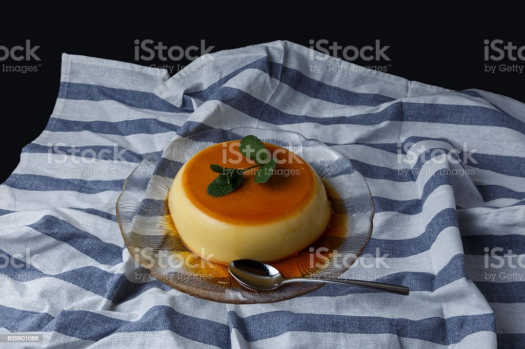 Vanilla flan served in glass dish on a kitchen cloth stock photo