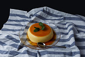 Vanilla flan served in glass dish on a kitchen cloth