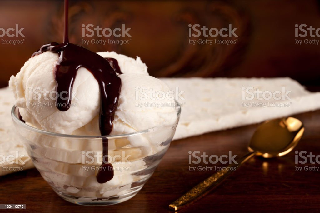 Vanilla ice cream with chocolate syrup, gold spoon stock photo