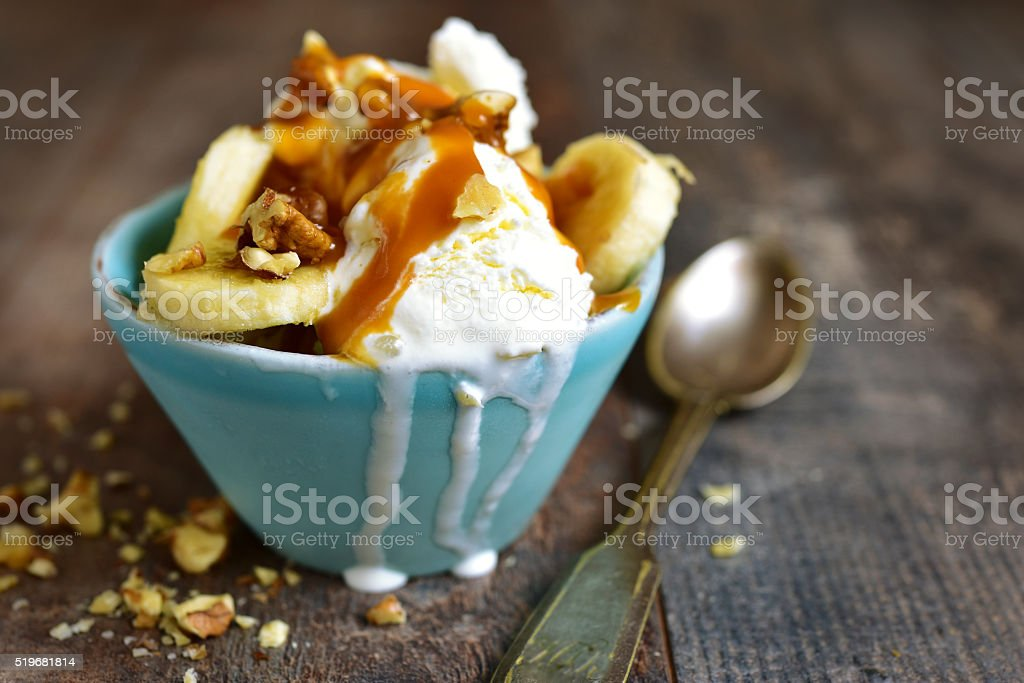 Vanilla ice cream with walnuts,banana and caramel. stock photo
