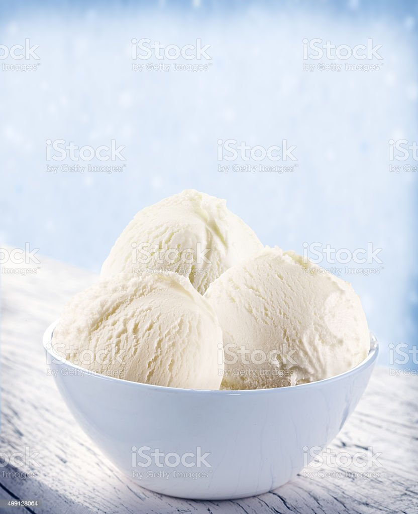 Vanilla ice-cream scoops in white cup over snow background. stock photo