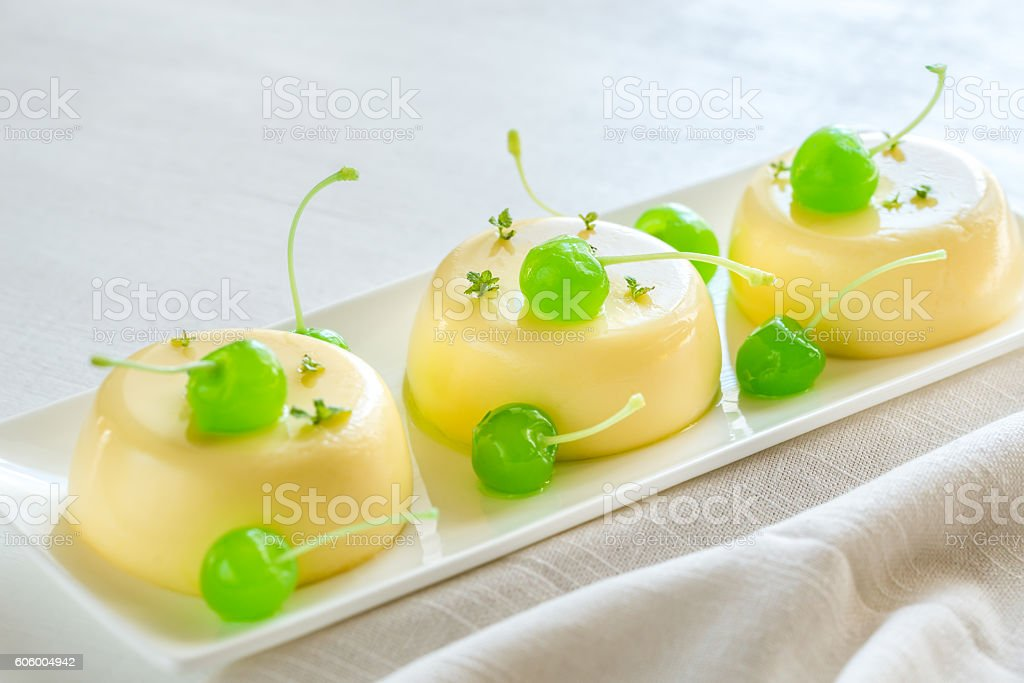 Vanilla puddings decorated with cocktail cherries stock photo