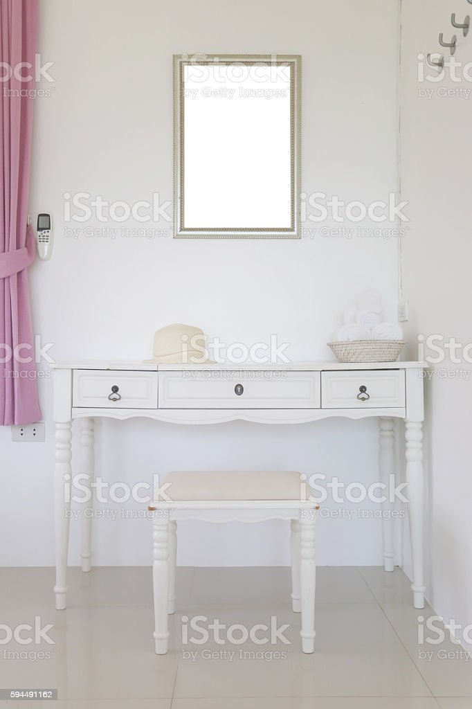 Vanity and have looking glass hanging on wall. stock photo
