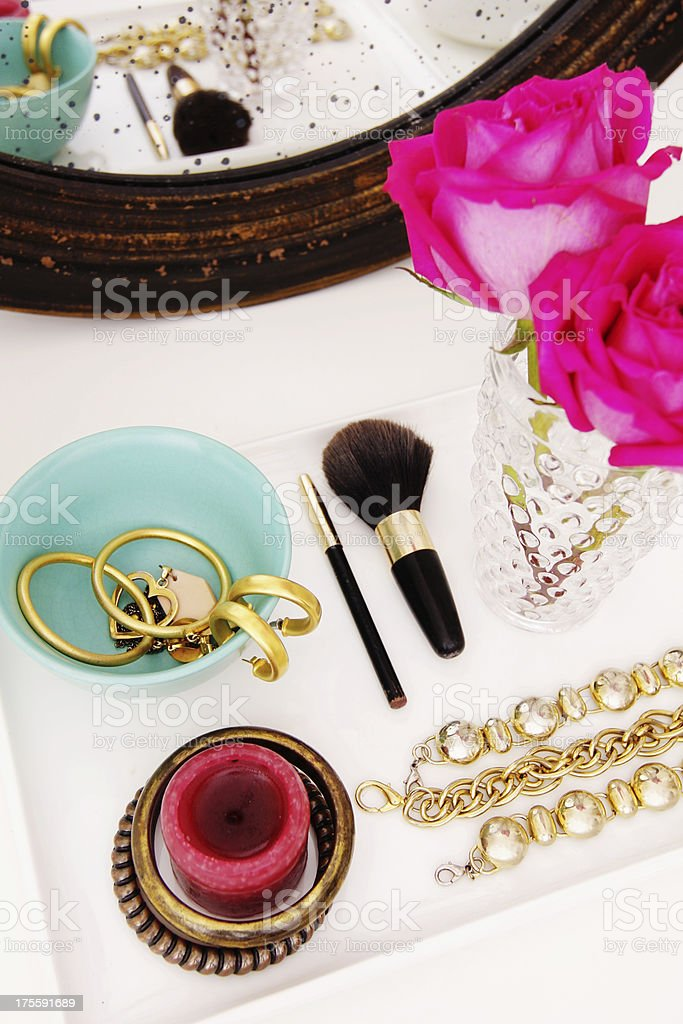 Vanity table with jewelry pieces and pink rose on vase stock photo