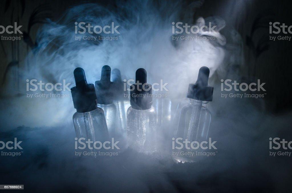 Vape concept. Smoke clouds and vape liquid bottles on dark background. Light effects. Useful as background or vape advertisement. stock photo