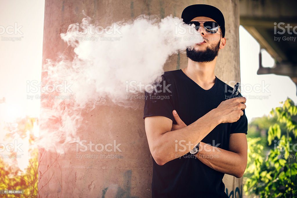 Vaper with beard in sunglasses vaping outdoor stock photo