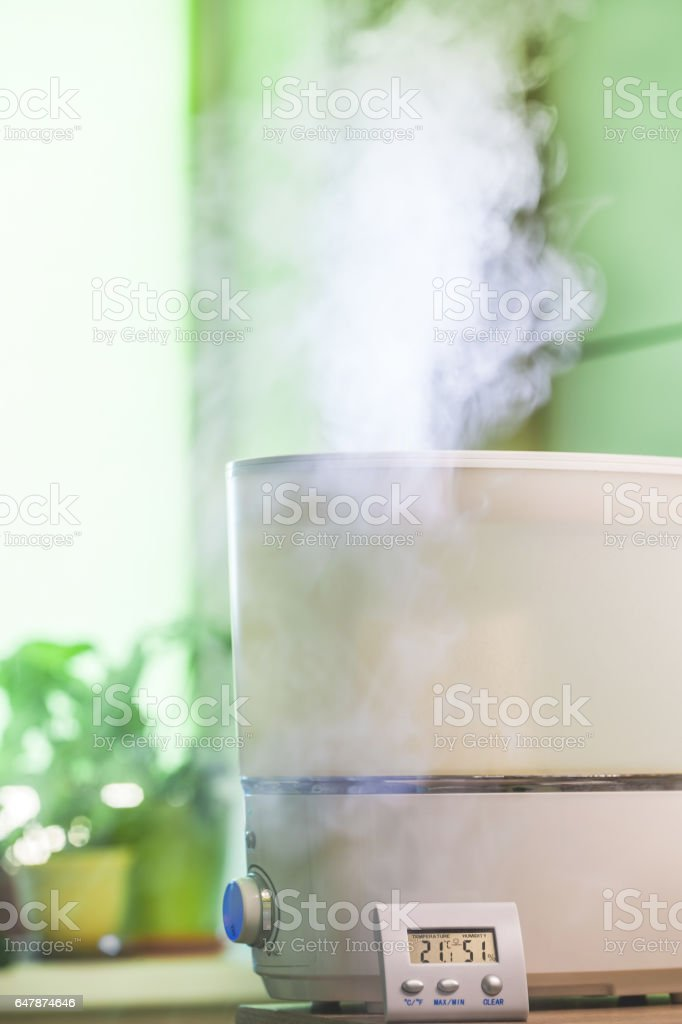 Vapor from humidifier in front of window and nygrometer stock photo