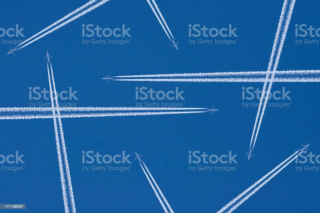 Vapor trails from airplanes in mid-air against a blue sky stock photo