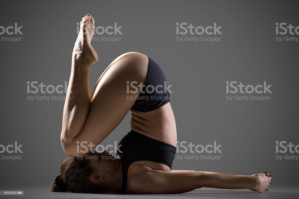 Variation of Knee to Ear Yoga Pose stock photo