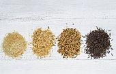 Varieties of Rice in piles on top of White Wood