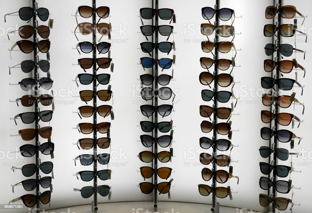Varieties of sunglasses on lighted wall stock photo