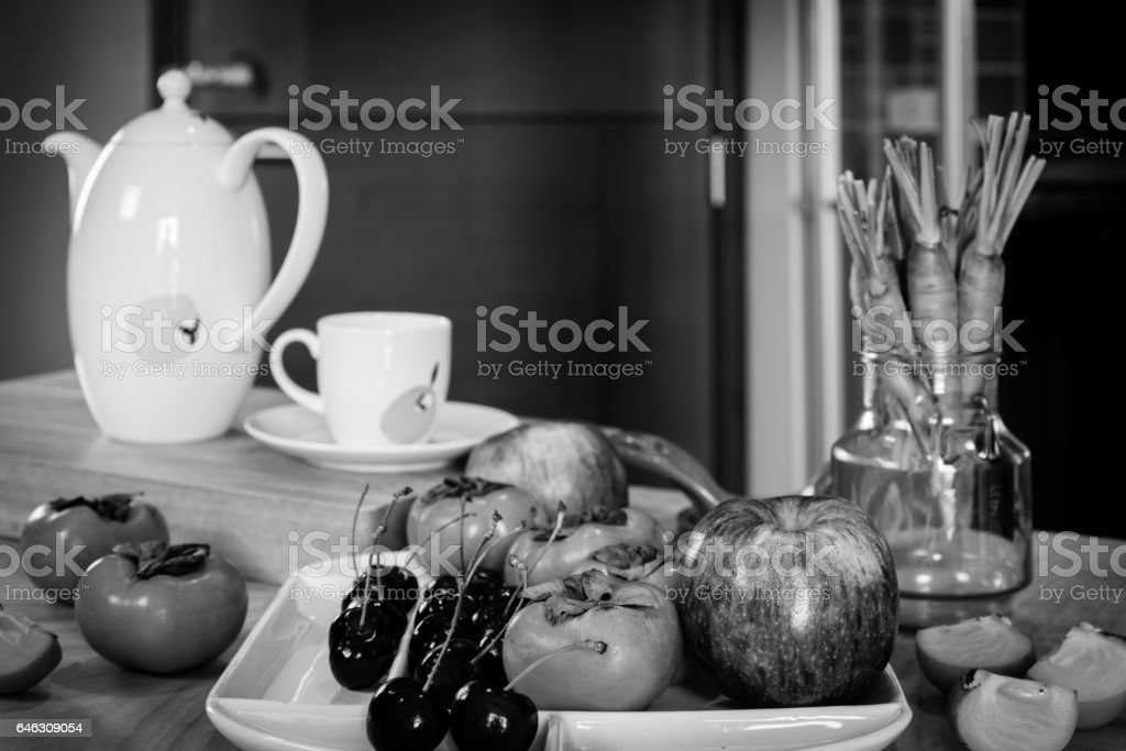 Variety fruits, tea pot on wooden table in modern kitchen / black and...