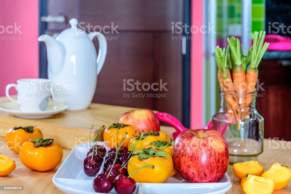 Variety fruits, tea pot on wooden table in colorful modern kitchen /...