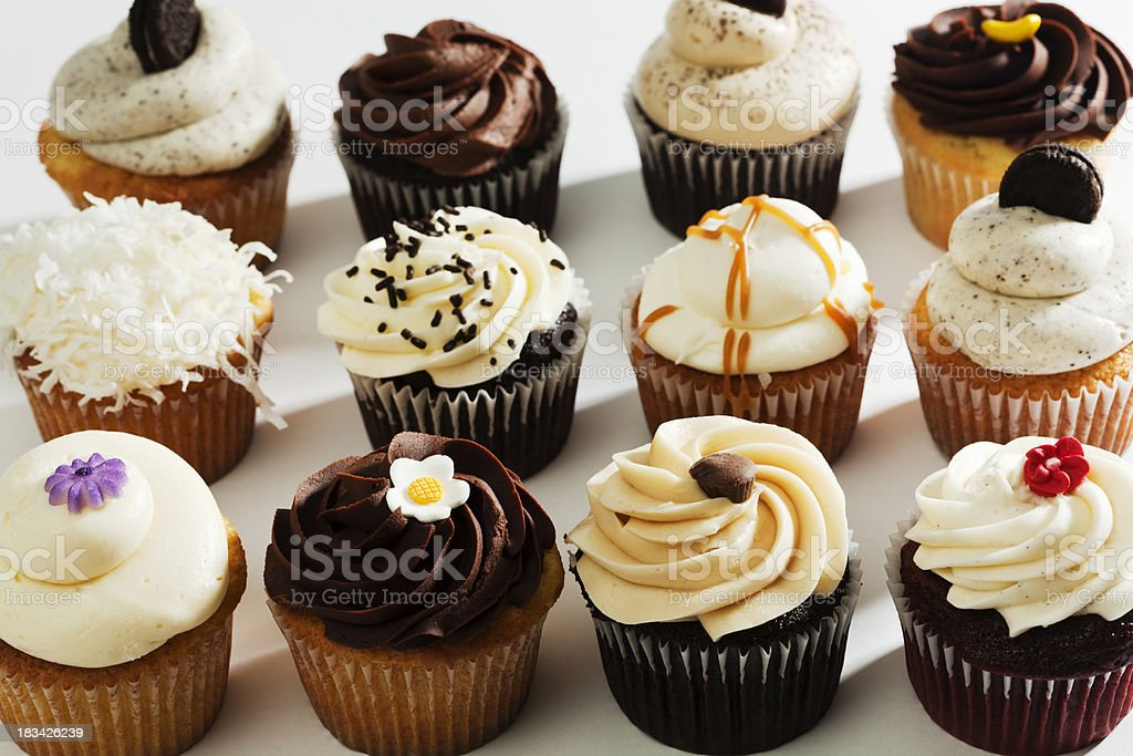 Variety of a Dozen Fancy Gourmet Frosted, Sprinkled, Decorated Cupcakes royalty-free stock photo