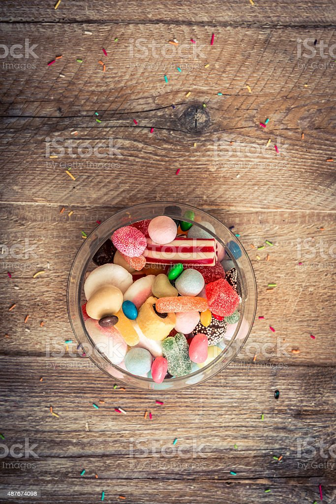 variety of candies on a wooden background stock photo