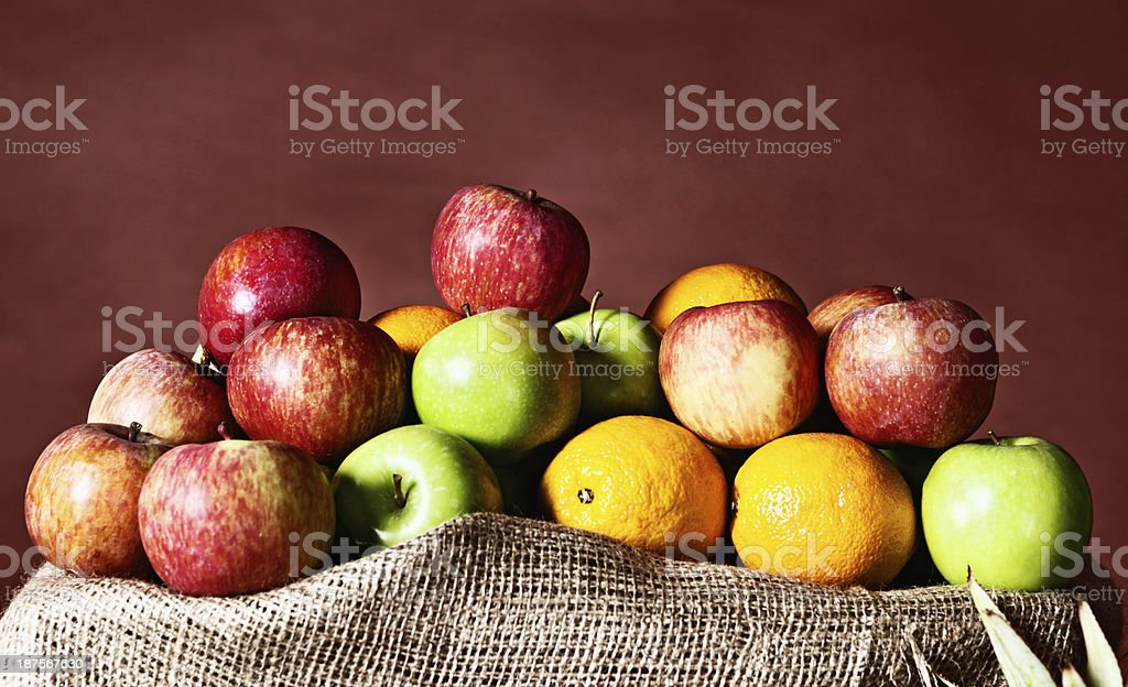 Variety of colorful apples and citrus fruit on burlap royalty-free stock photo