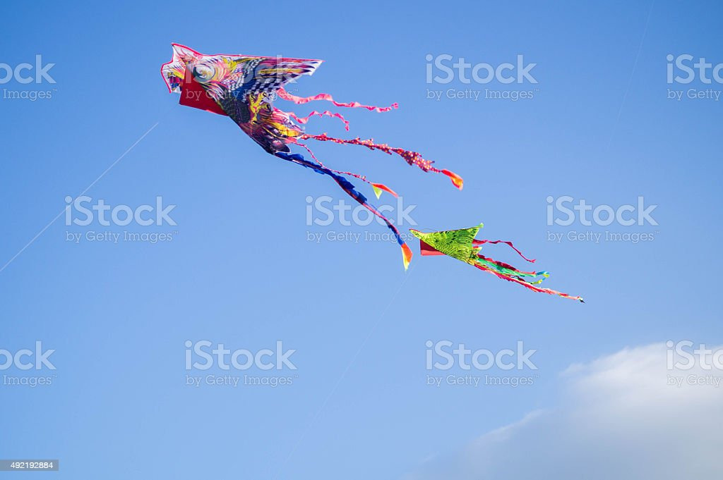 Variety of colorful Kites in a clear blue sky stock photo