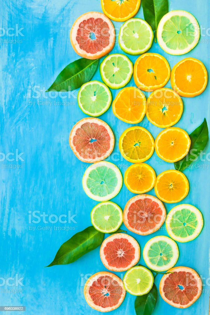 Variety of colorful sliced citrus fruits oranges, grapefruits, lemons, limes with green leaves on blue background, styled composition, abstract, flat lay, copy space stock photo