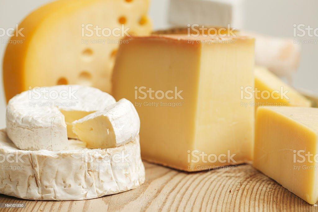 A variety of cut cheeses on a butcher block stock photo