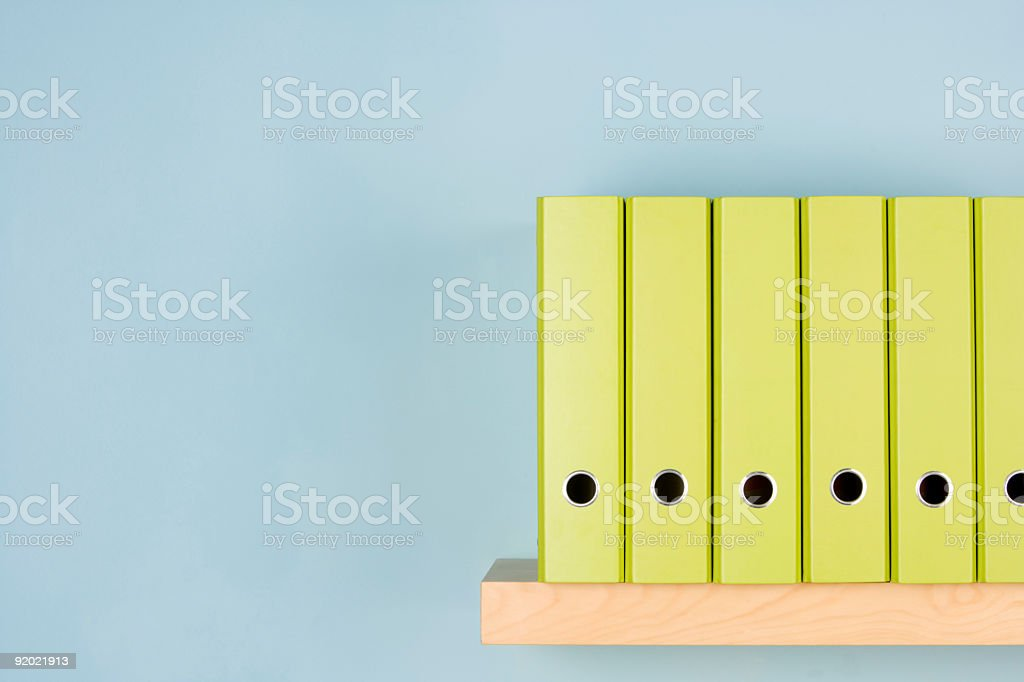 A variety of different green binders in a row on a shelf royalty-free stock photo