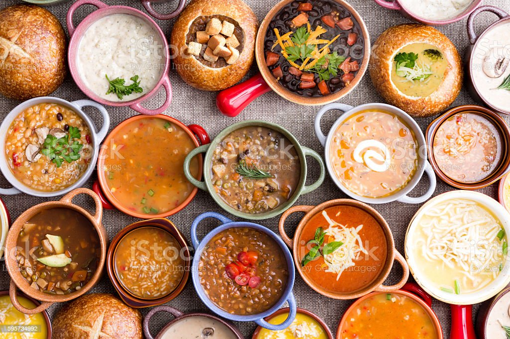 Variety of Garnished Soups in Colorful Bowls stock photo