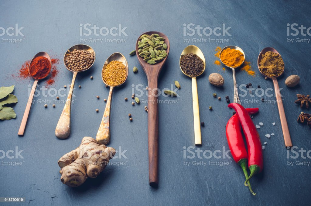 Variety of herbs and spices on slate background. stock photo