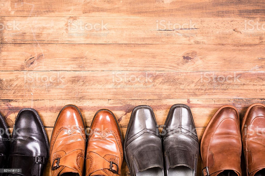 Variety of men's shoes in a row. Closet. No people. stock photo