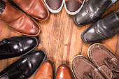 Variety of men's shoes in circle. Closet. No people.