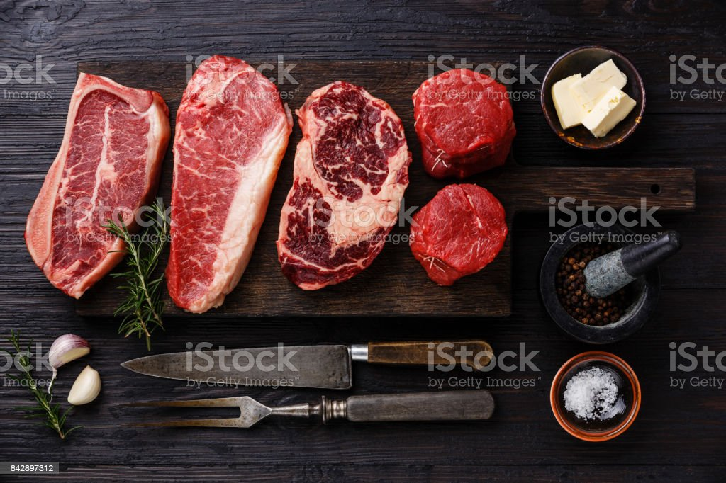 Variety of Raw Black Angus Prime meat steaks and seasoning stock photo