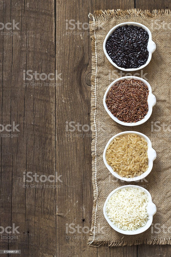 Variety of rice in bowls on wooden table stock photo