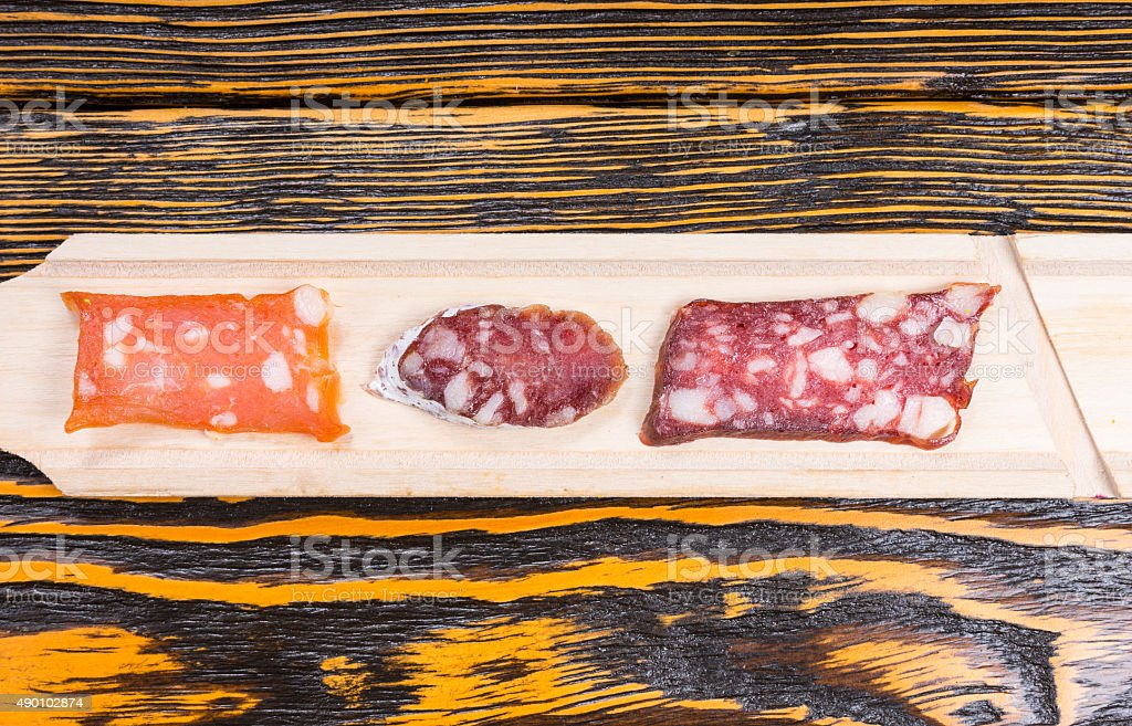 Variety of Sliced Gourmet Meats on Long Wood Board stock photo