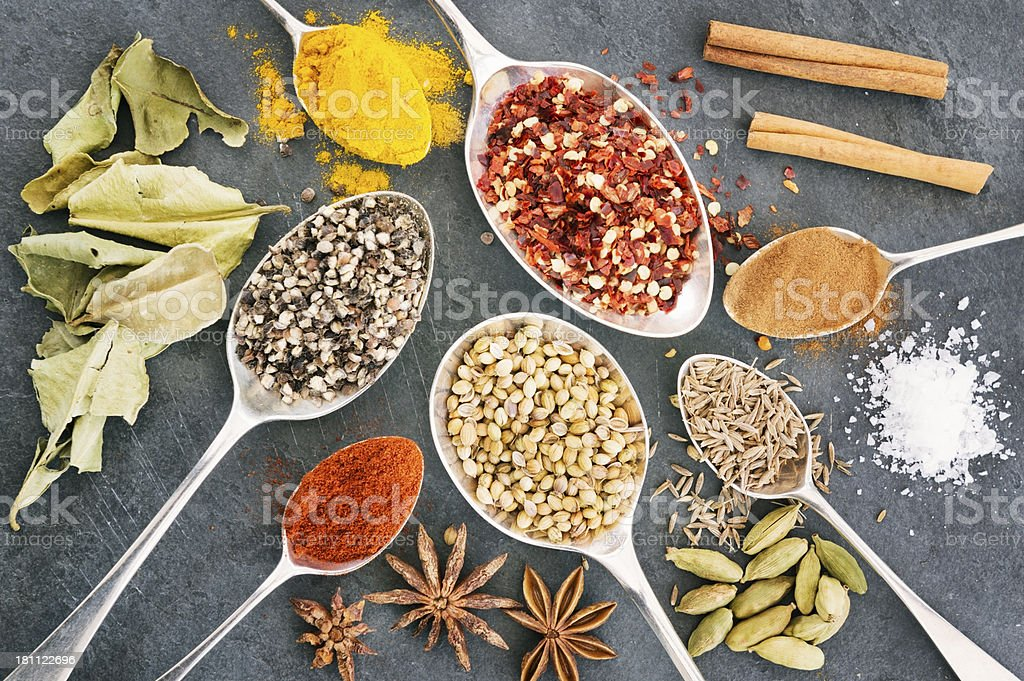 variety of spices in old spoons on slate background royalty-free stock photo