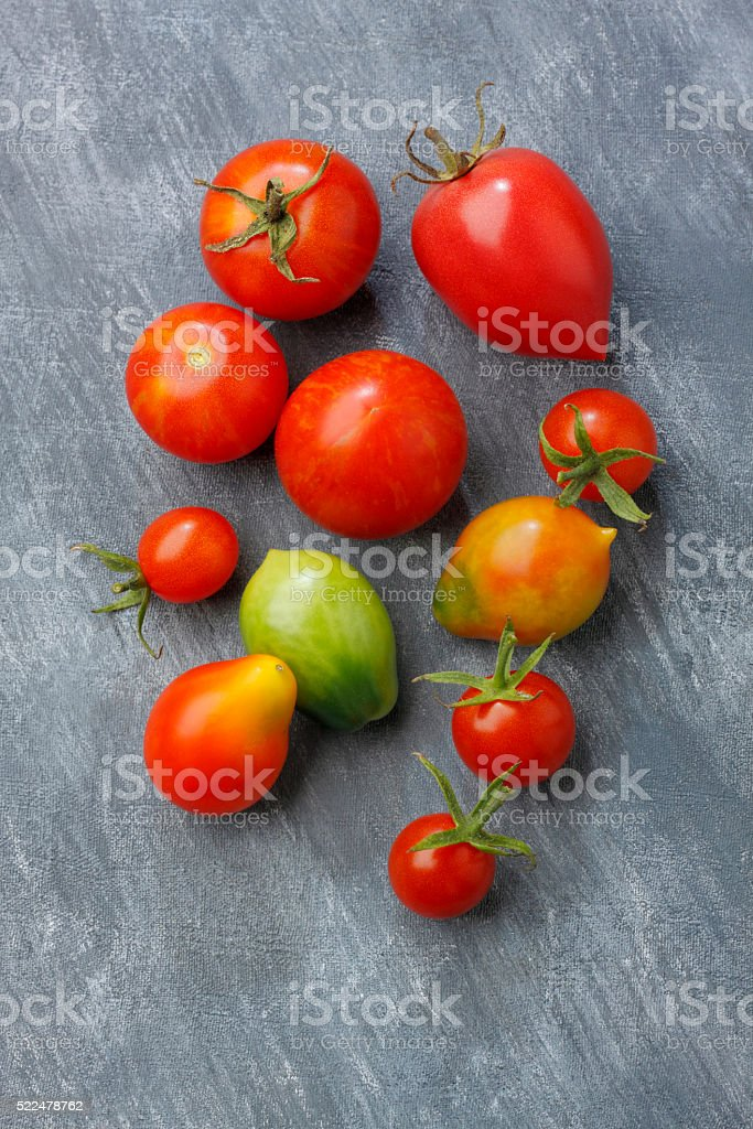 Variety of tomato fruits over painted textile background stock photo
