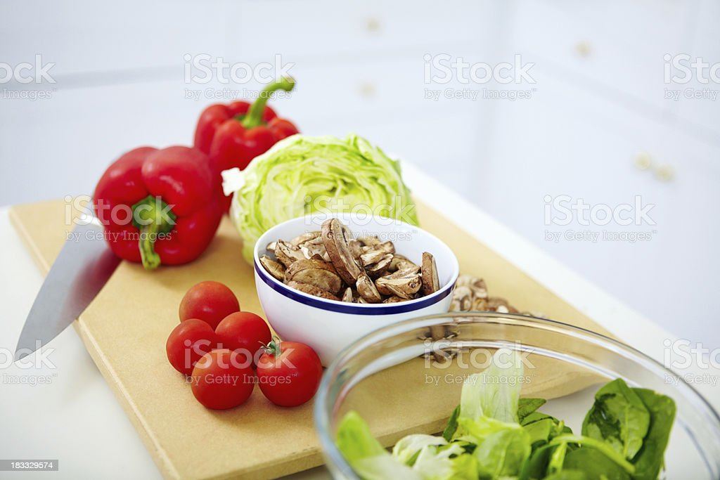 Variety of vegetables on cutting board with a knife royalty-free stock photo