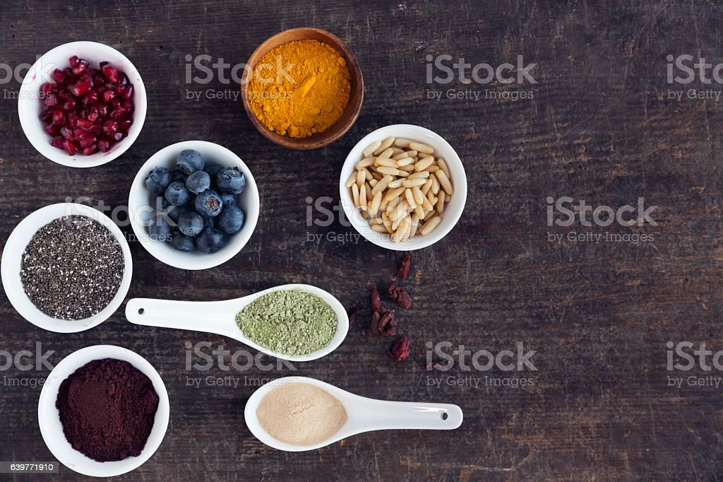 various antioxidant superfoods in  bowls on dark wood stock photo