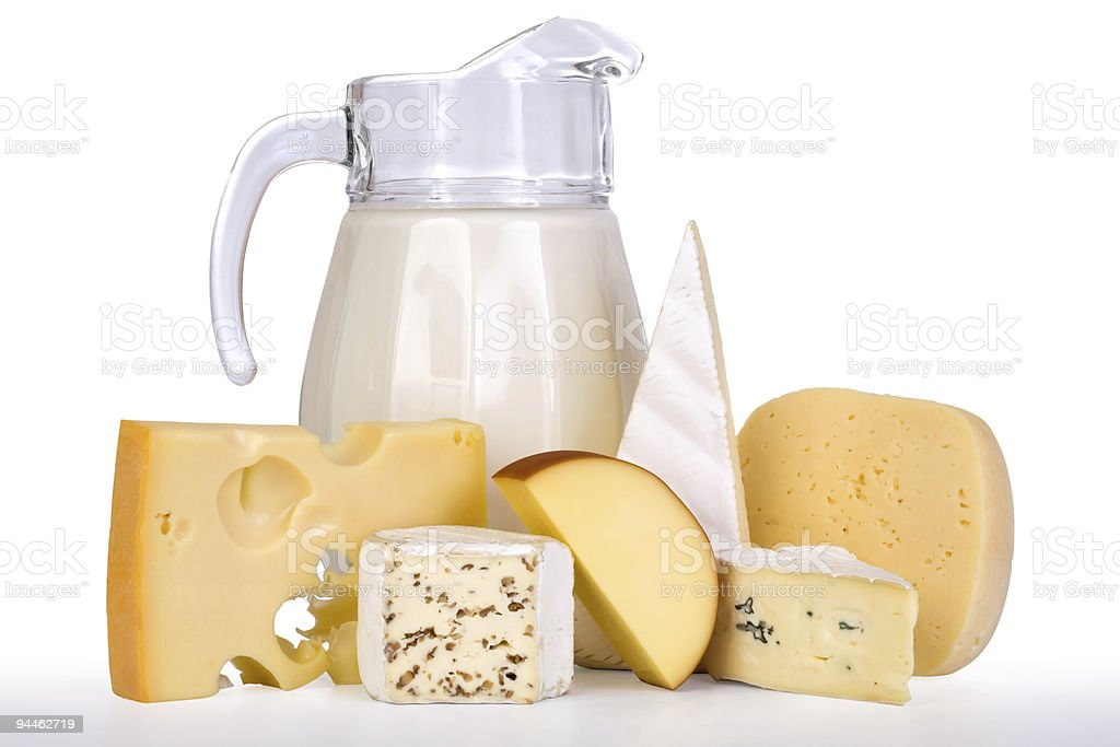 Various blocks of cheese with a pitcher of milk stock photo