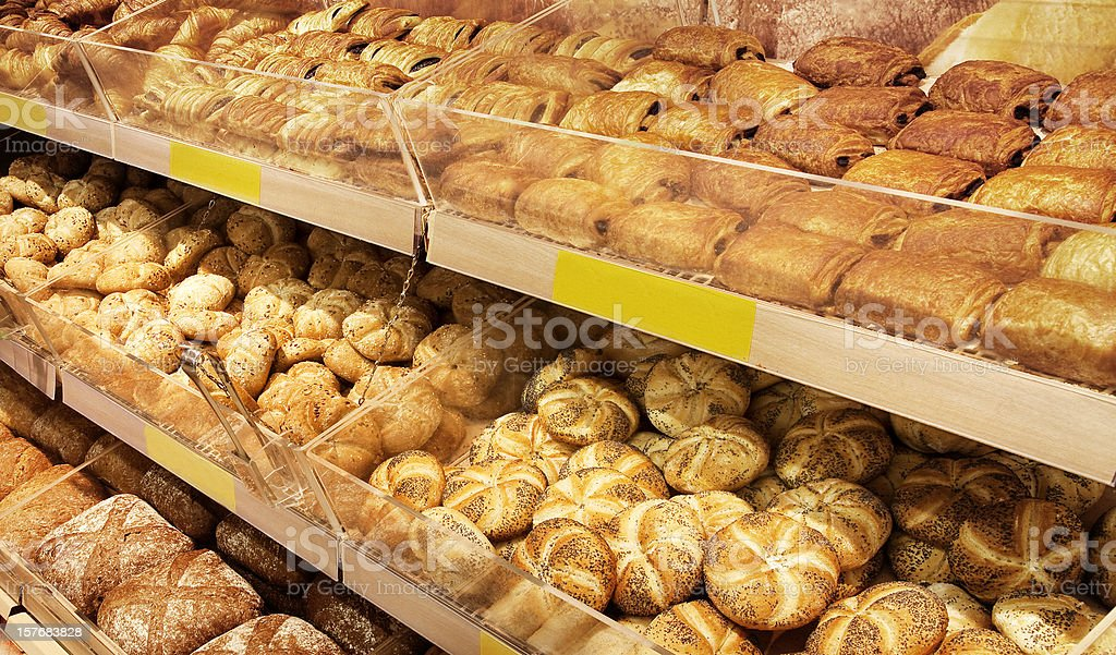 Various breads sitting on a large shelf stock photo