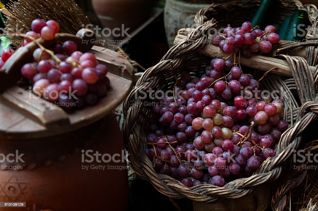 various bunches of red grapes on wicker basket stock photo