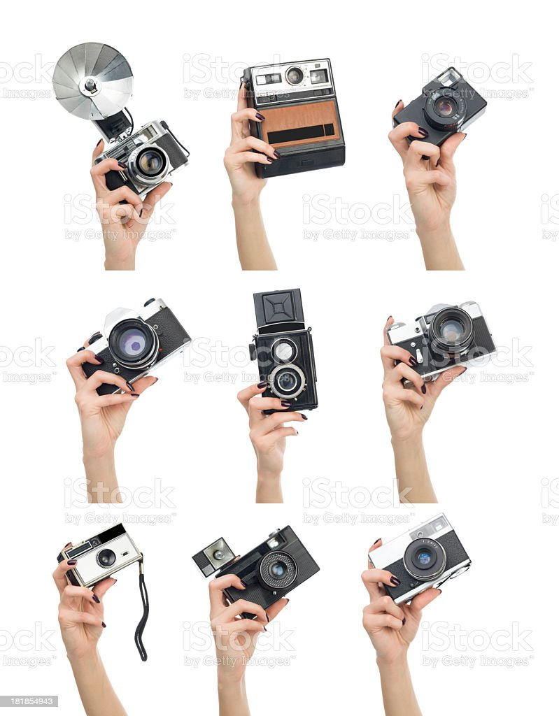 Various cameras in human hand on white background stock photo