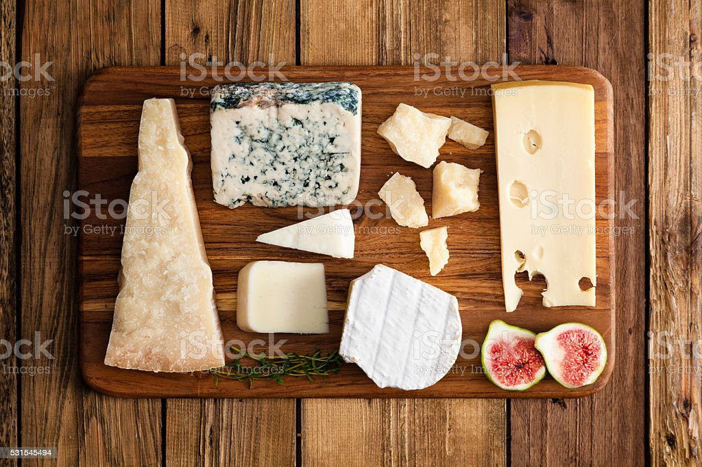 Various cheeses on a wood tray stock photo