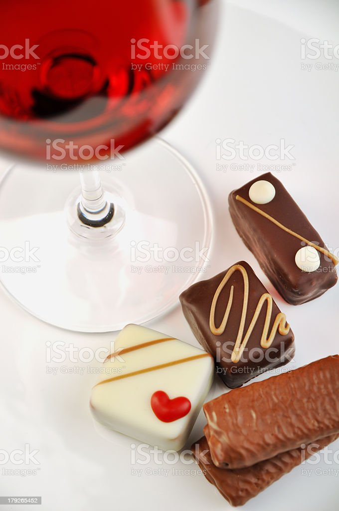 Various chocolates and a glass of wine on white background royalty-free stock photo