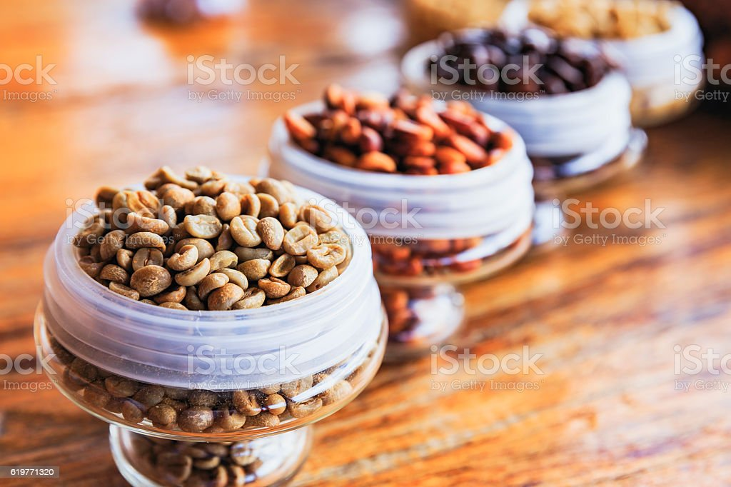 Various coffee beans on wooden background. stock photo